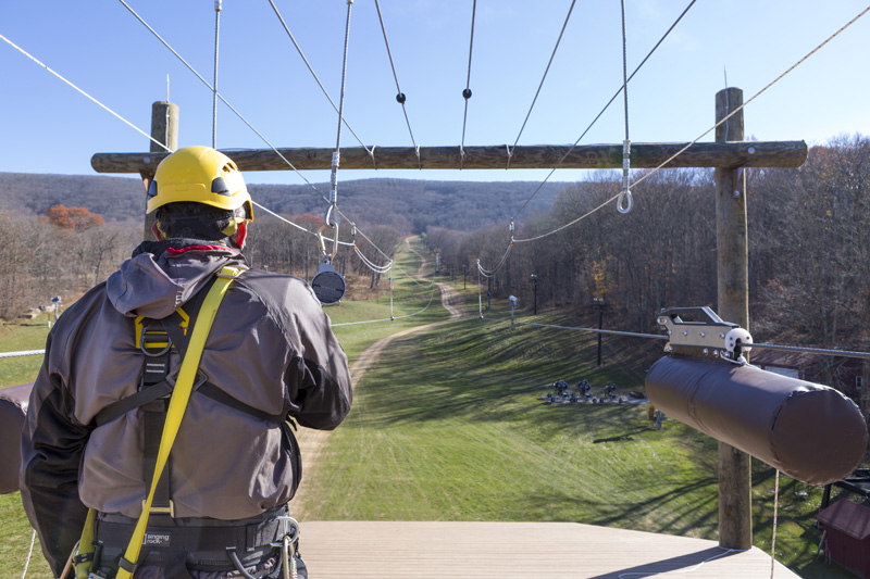 Man getting ready to zipline off a platform.