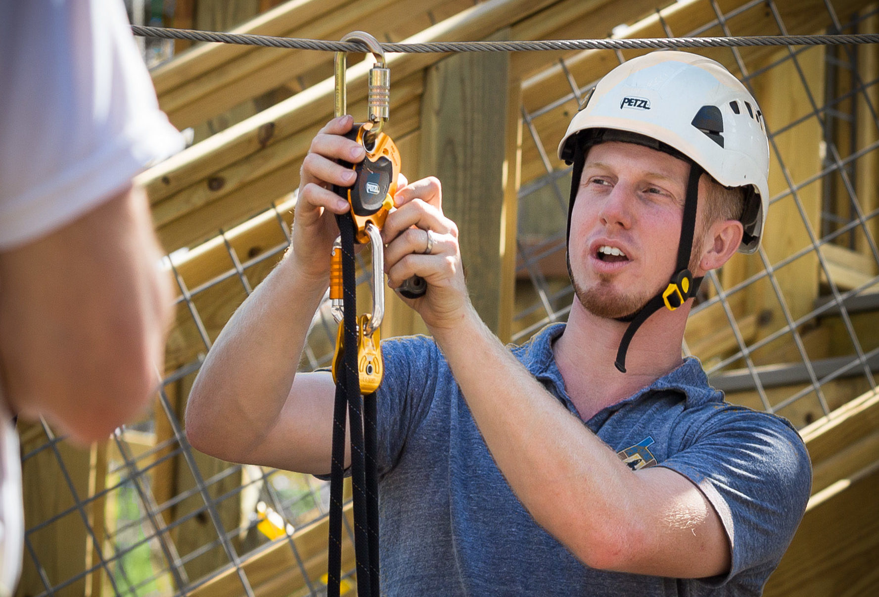 Man demonstrating how to use a belay system.