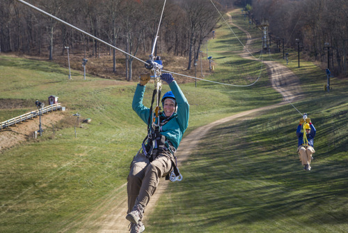 Smiling person zip lining.