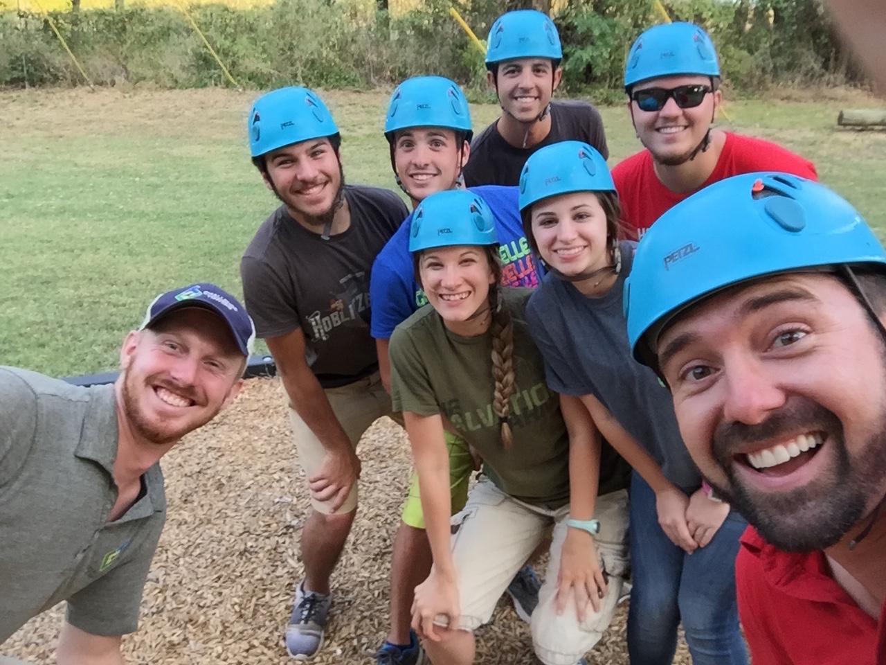Group of smiling people wearing helmets.