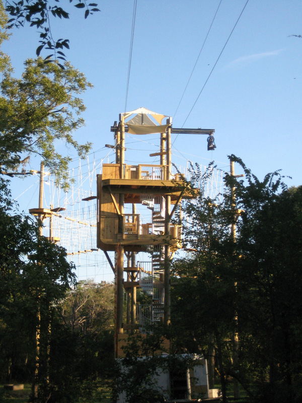 Challenge course tower with stairs and zipline extending out.