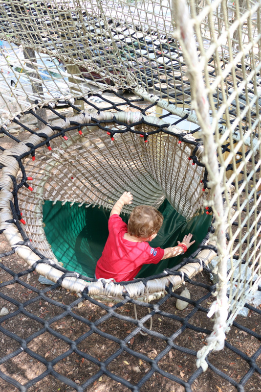 Boy sliding through net course slide.