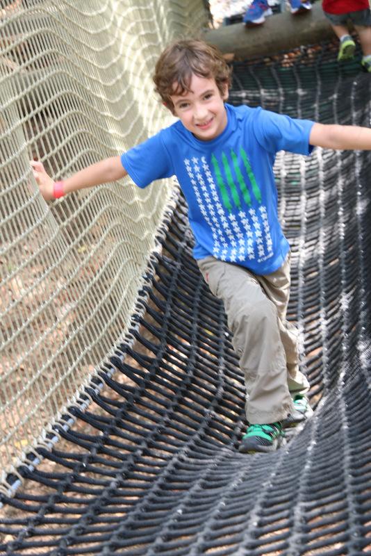 Boy climbing the nets in a Skynet course.