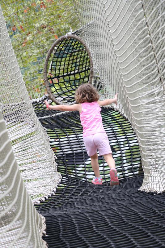 Girl running through net course.