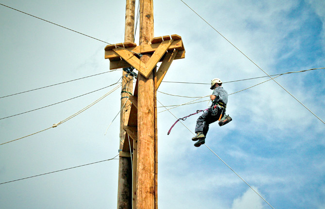 Man repairing a wire in the air.
