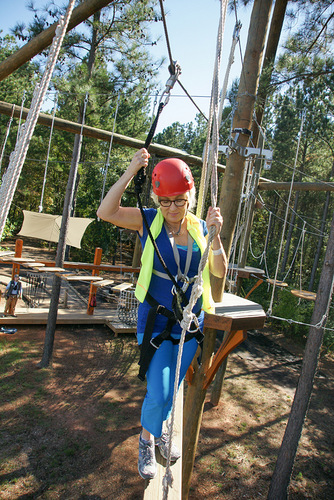 Woman walking across an aerial adventure course feature.