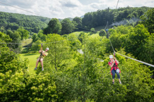 Man and woman zip lining over a green field.