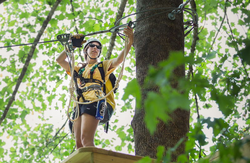 Girl attaching belay to zip line.