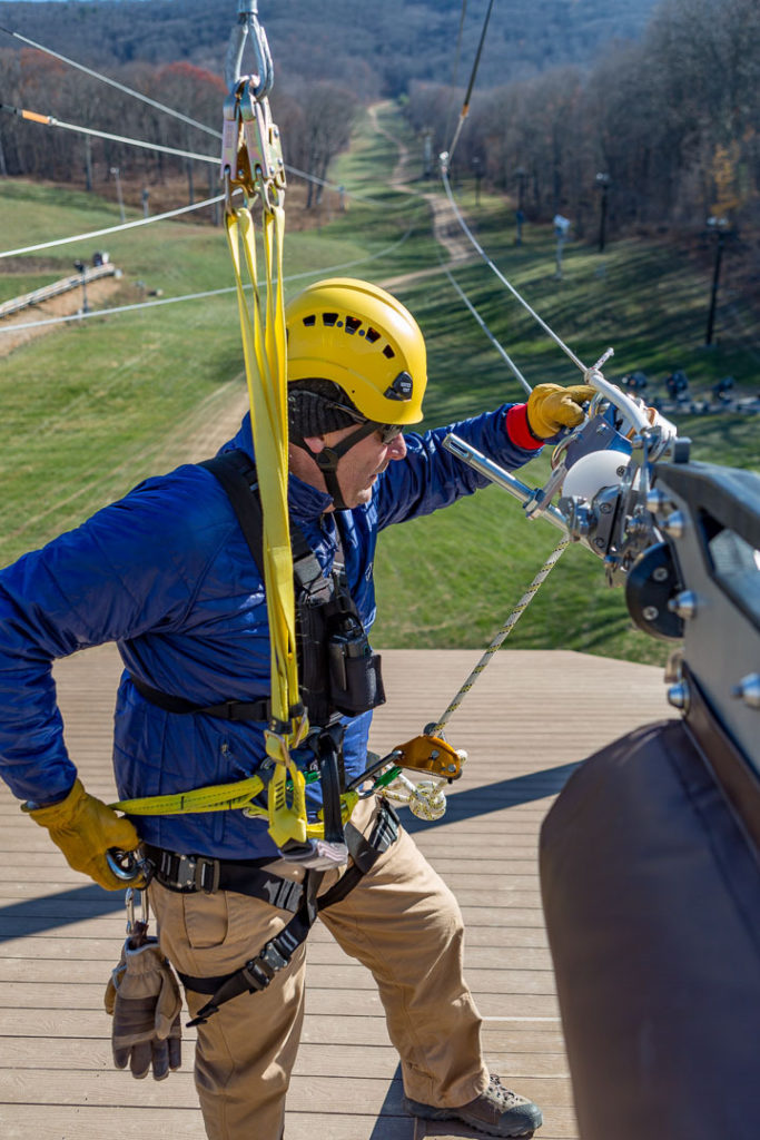 Man performing maintenance on zip line course