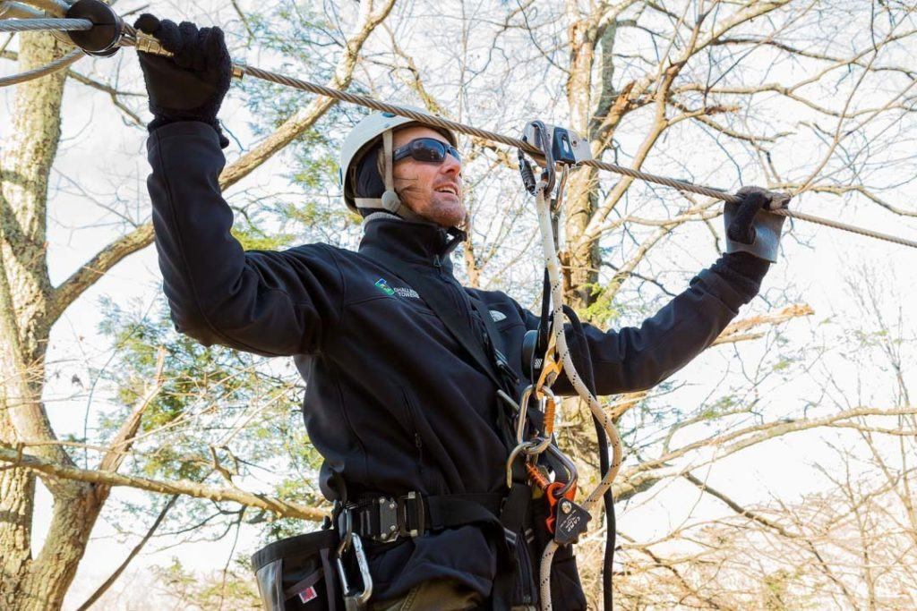 Man checking zip line on course