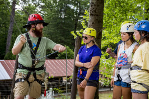 Trainer instructing camp staff on proper belay techniques