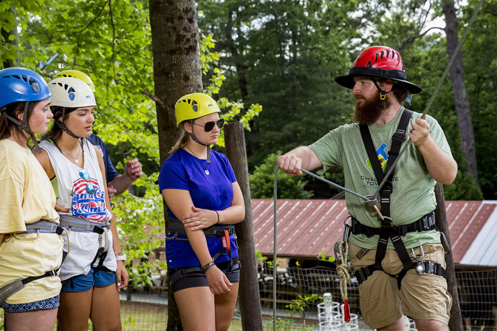 Trainer instructing camp staff on proper belay techniques - in Summer